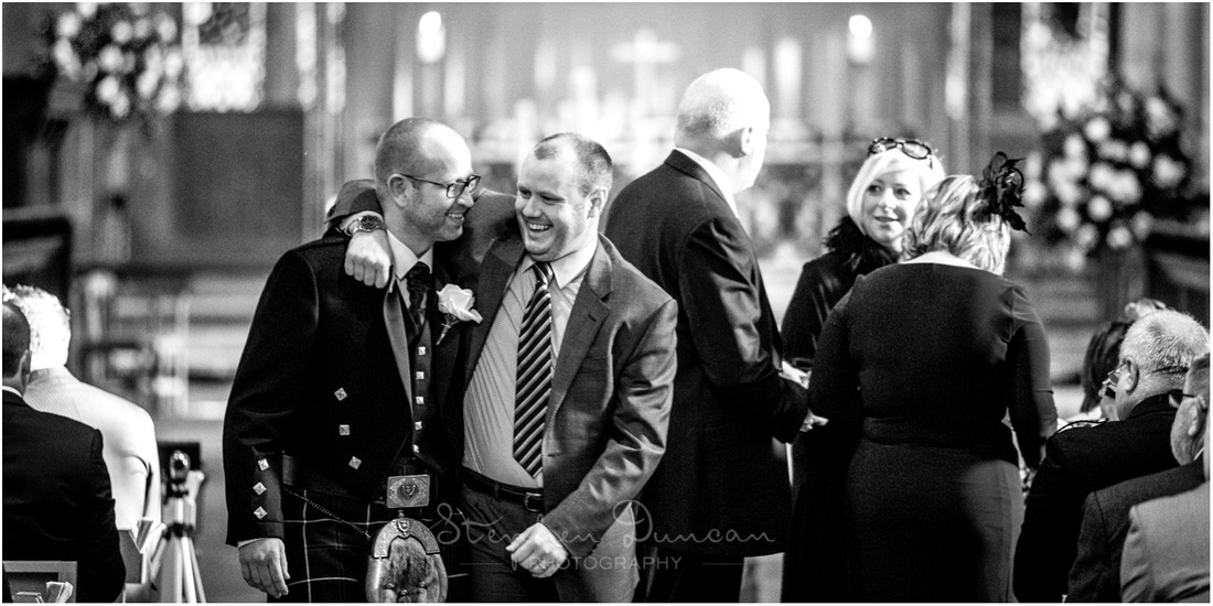 Black and white image of groom with guest inside church before the ceremony