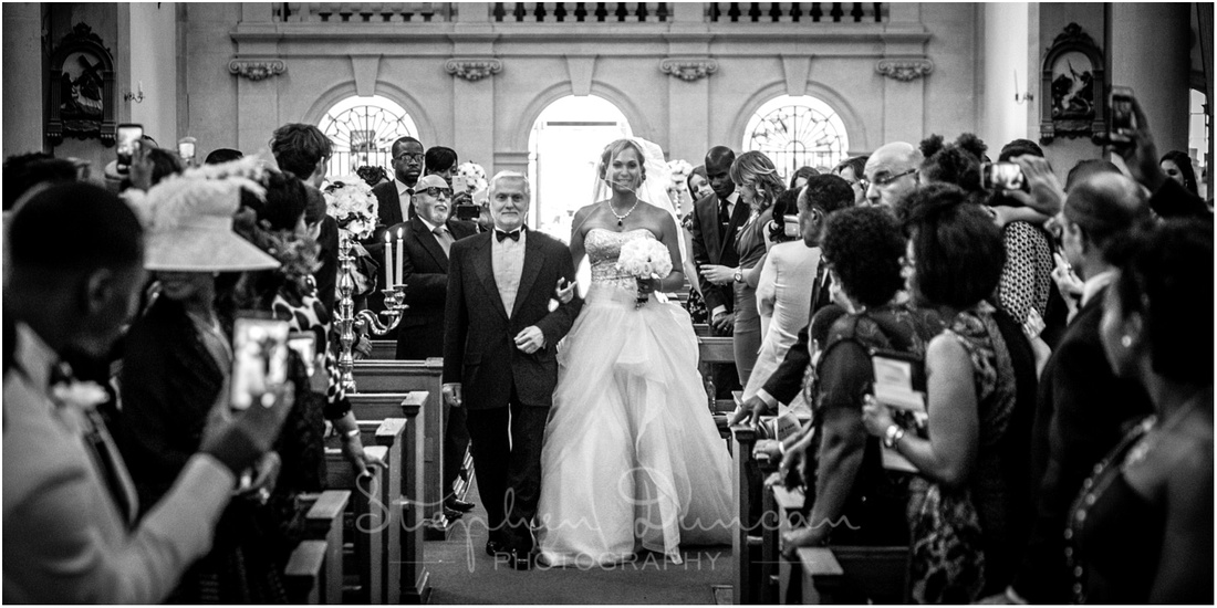 The bride walks down the aisle on her father's arm at St Bridgets of Sorrows Church Brentford