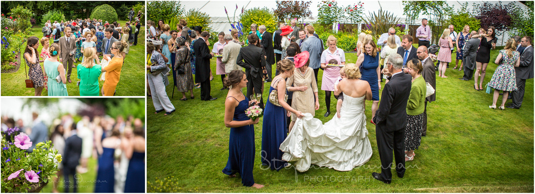 Guests enjoying themselves in the garden with the marquee in the background