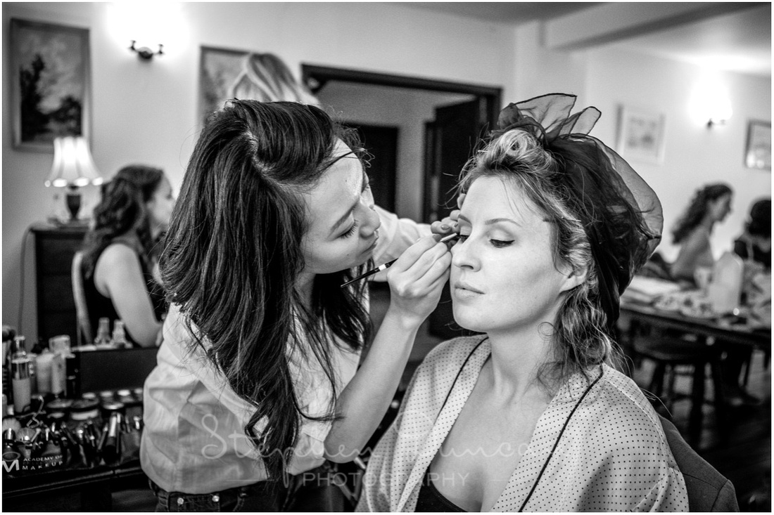 Black and white photo of bride having make-up applied