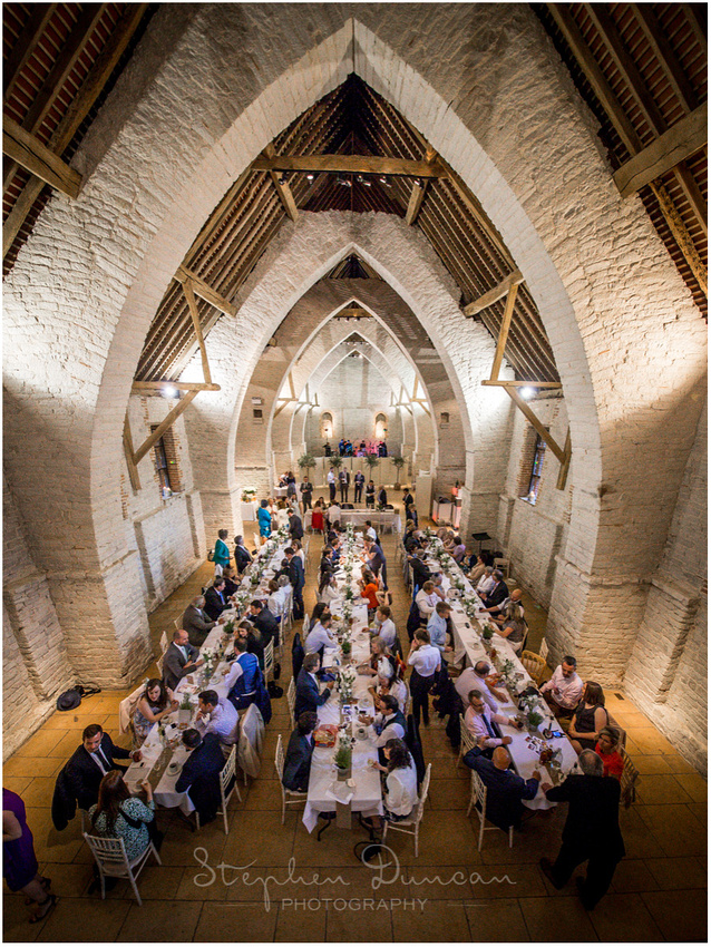 Wide-angle view from balcony of the barn during the wedding breakfast, with tables et up in a banqueting style