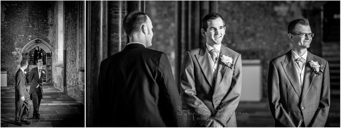 Black and white photo of groom and best man inside hall to welcome guests as they arrive