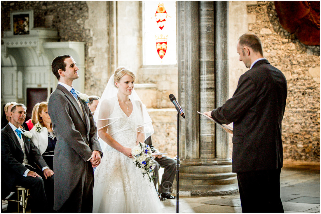 The bride and groom at the start of the wedding ceremony, stood at the front of the Great Hall in Winchester