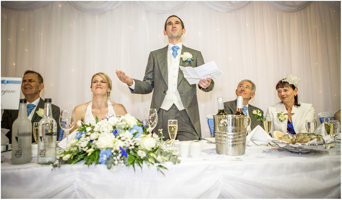 The groiomn stands at the top table to begin his wedding speech