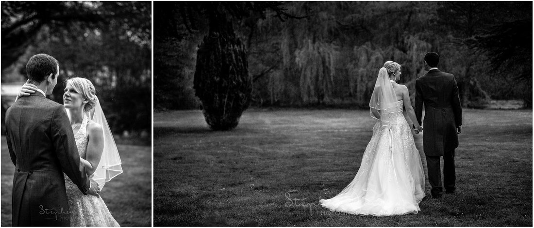 Black and white photo of bride and groom walking towards willow tress in garden by Manor House and lake