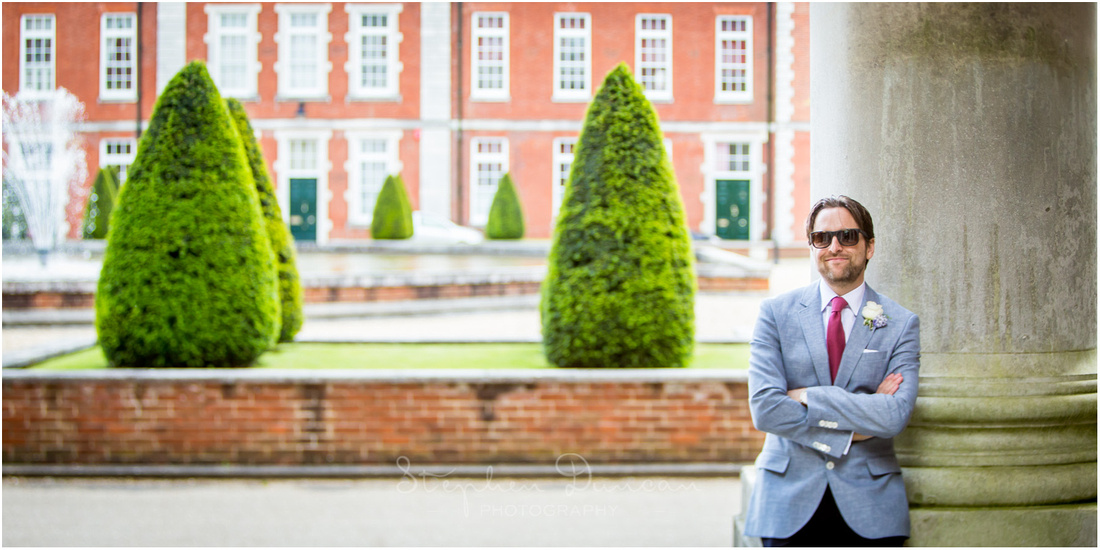 Colour photo of groom posing alone in front of the central fountain at Winchester's Peninsula Barracks