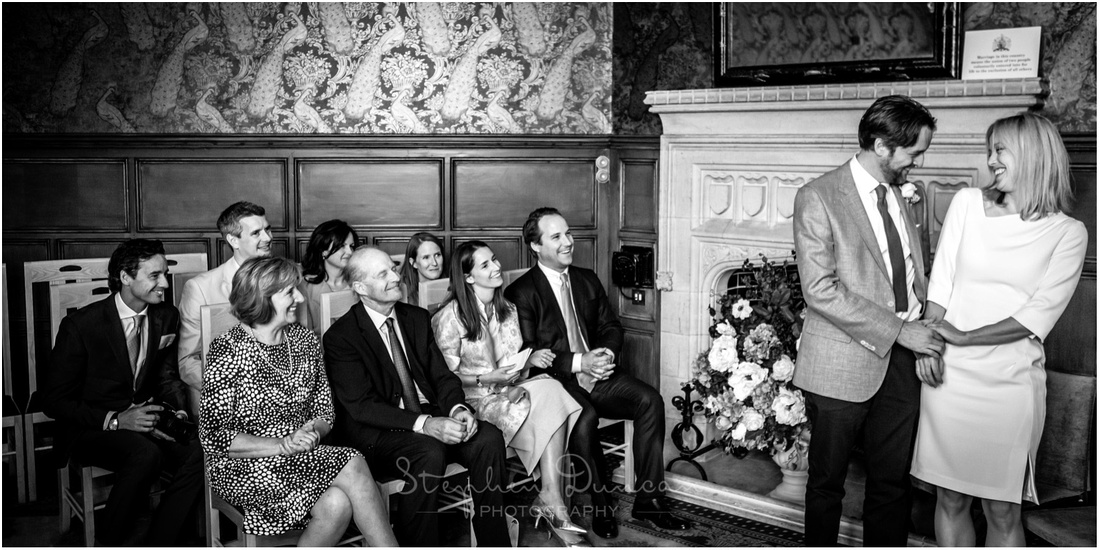 Black and white photo of the couple immediately after they become husband and wife, with wedding guests watching on