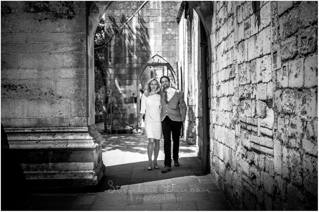 The bride and groom walk together through the iconic cloisters on the south side of Winchester Cathedral