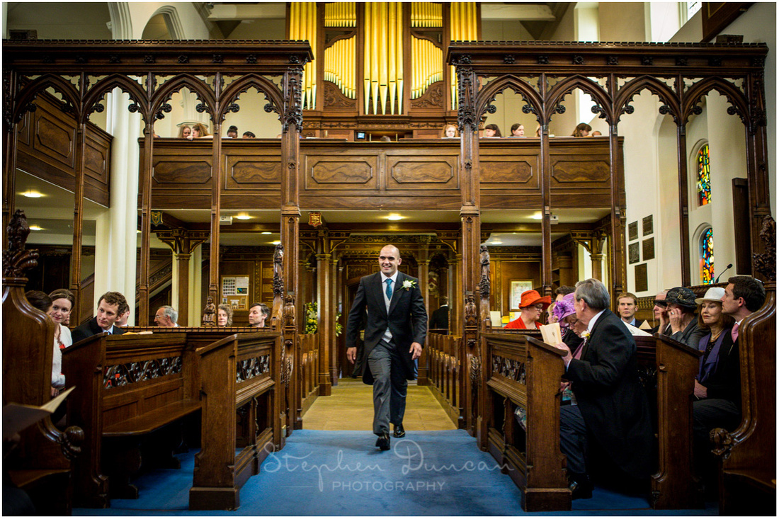 The groom walks through the chapel to take his position at the front ready for the arrival of the bride