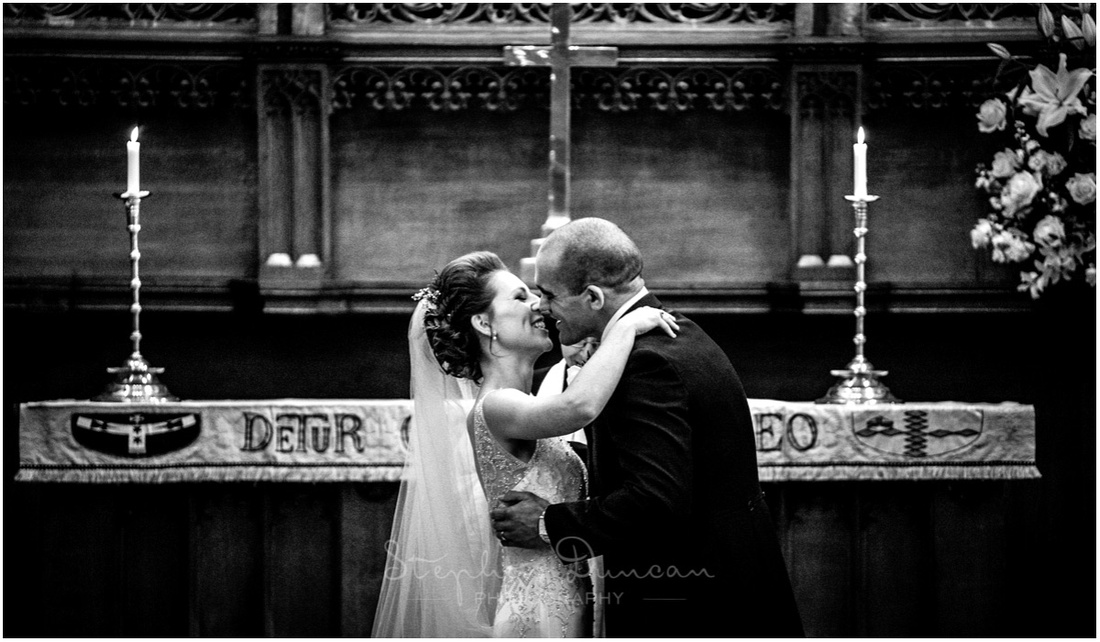 The newly married couple kiss in front of the altar in Christ's Church Chapel, Dulwich, London