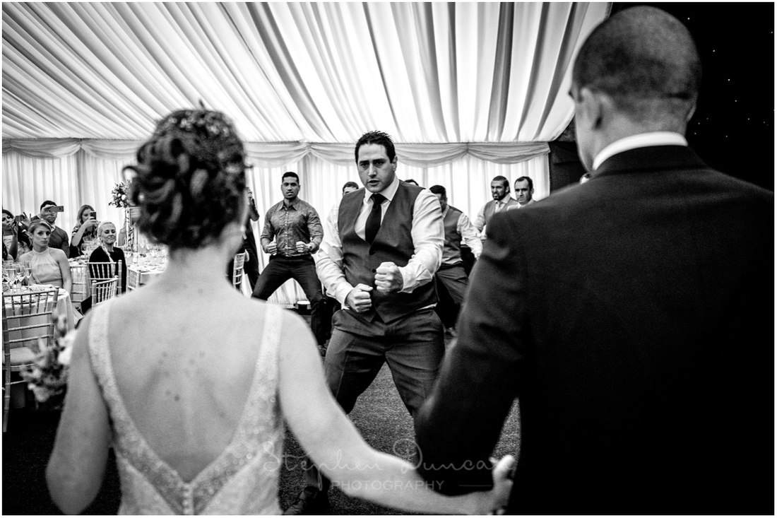 The bride and groom are welcomed to the reception with a traditional haka