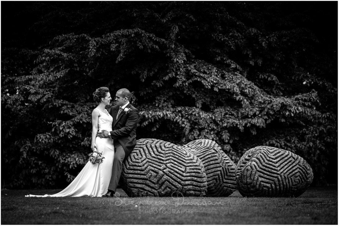 Bride and groom posed in front of sculptural feature in the grounds of Dulwich Picture Gallery