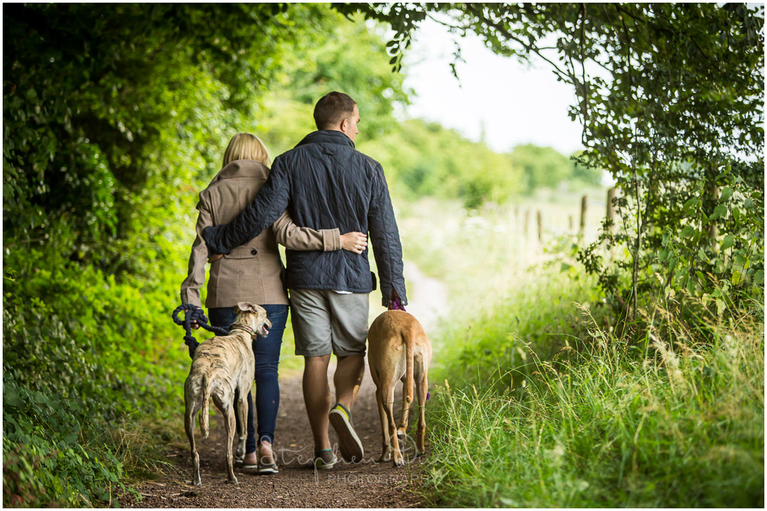 Couple and dogs walking away from camera towards open countryside