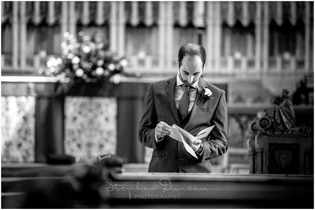 Black and white image of best man reading the order of service