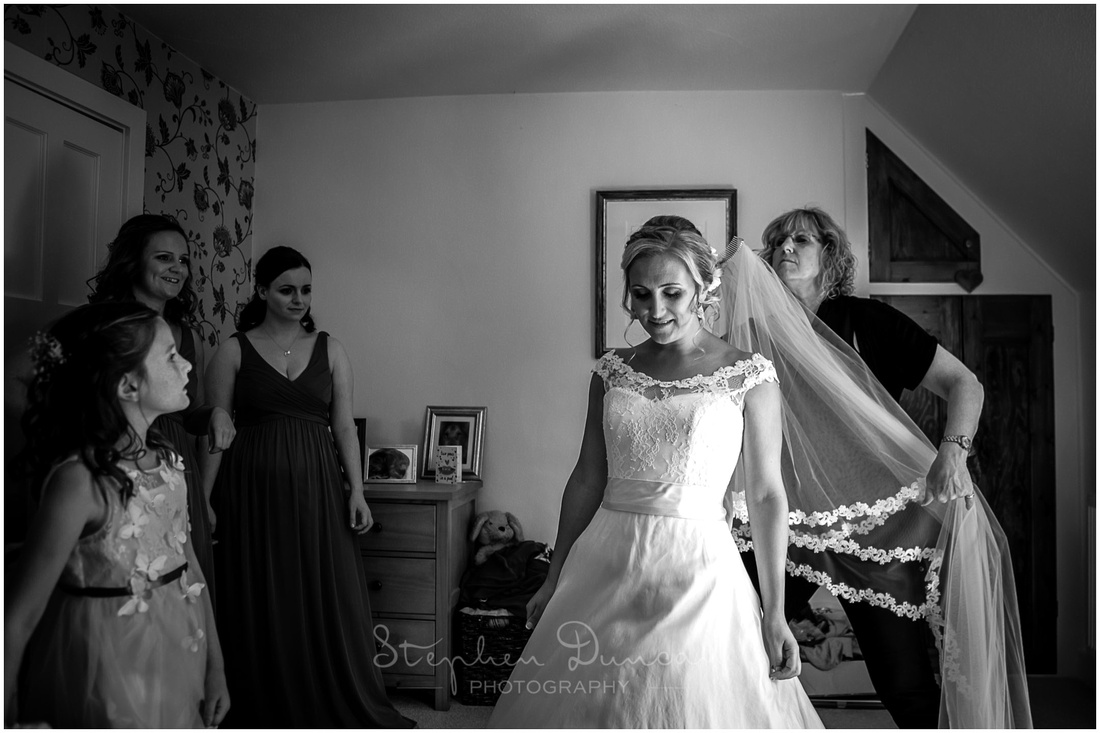 Black and white photo of bride with bridesmaids as she gets ready for the wedding