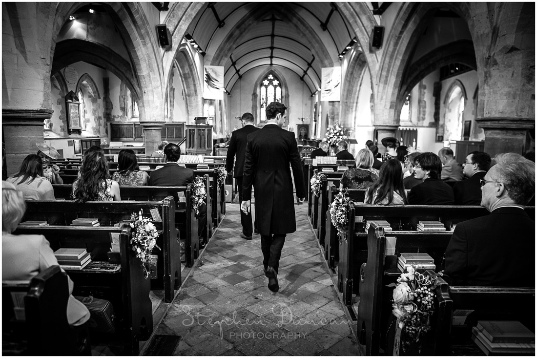 The groom walks down the central aisle to the front of the church