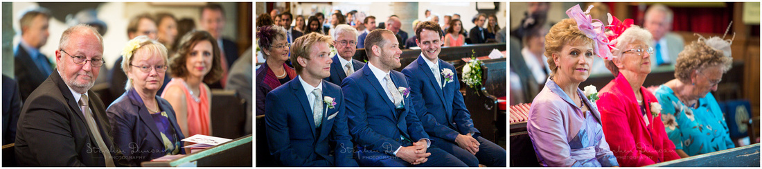 The groom is surrounded by family as he awaits the start of the wedding ceremony