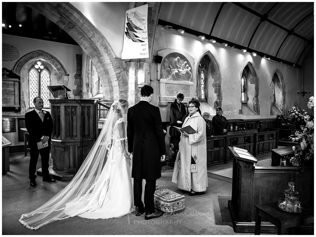The bride and groom stand together at the front of the church as the marriage ceremony begins