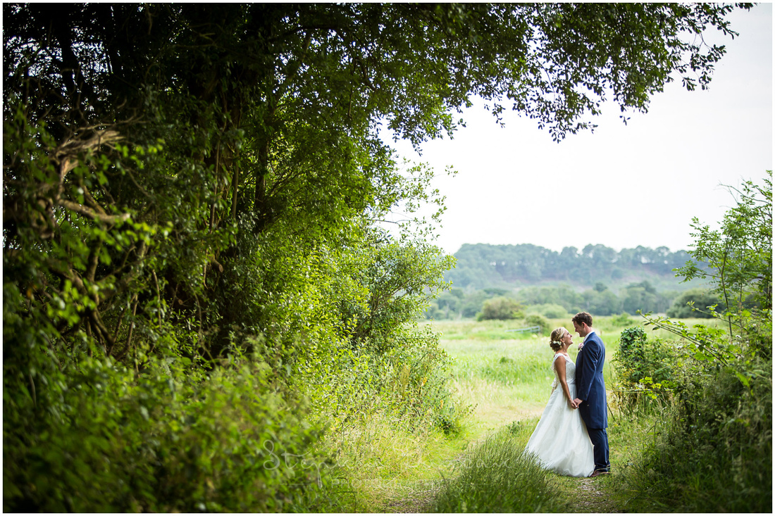 Bride and groom stand at the end of a small track leading towards open countryside in rural Dorset