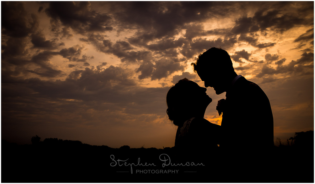 Silhouette of wedding couple at dusk by riverside