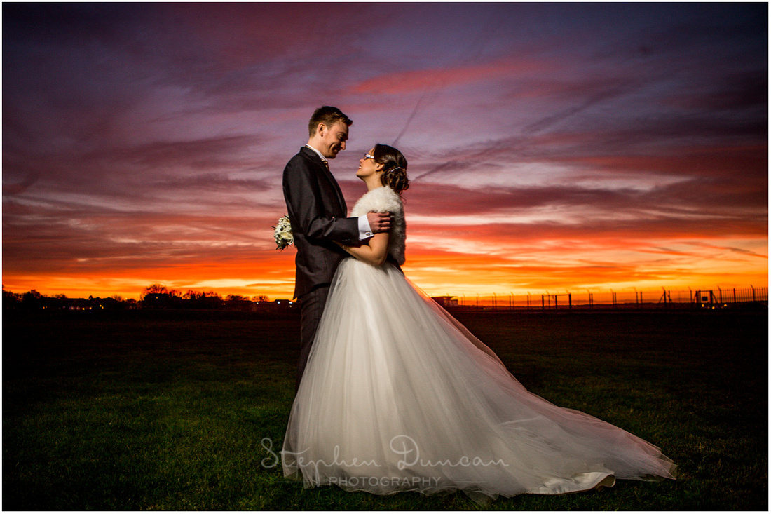Bride and groom outdoors at sunset