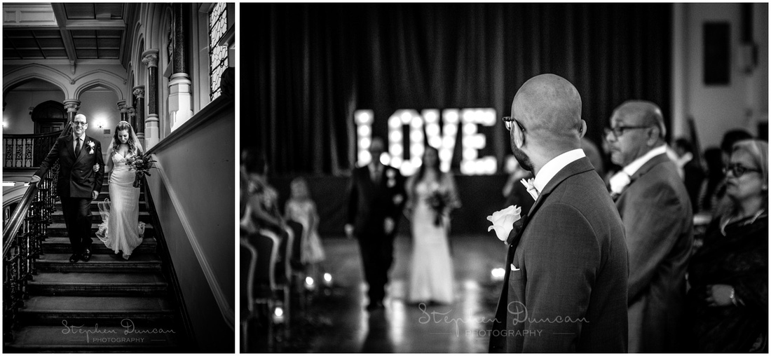 Bride walks down stairs and down the aisle on her father's arm as the groom waits at the front