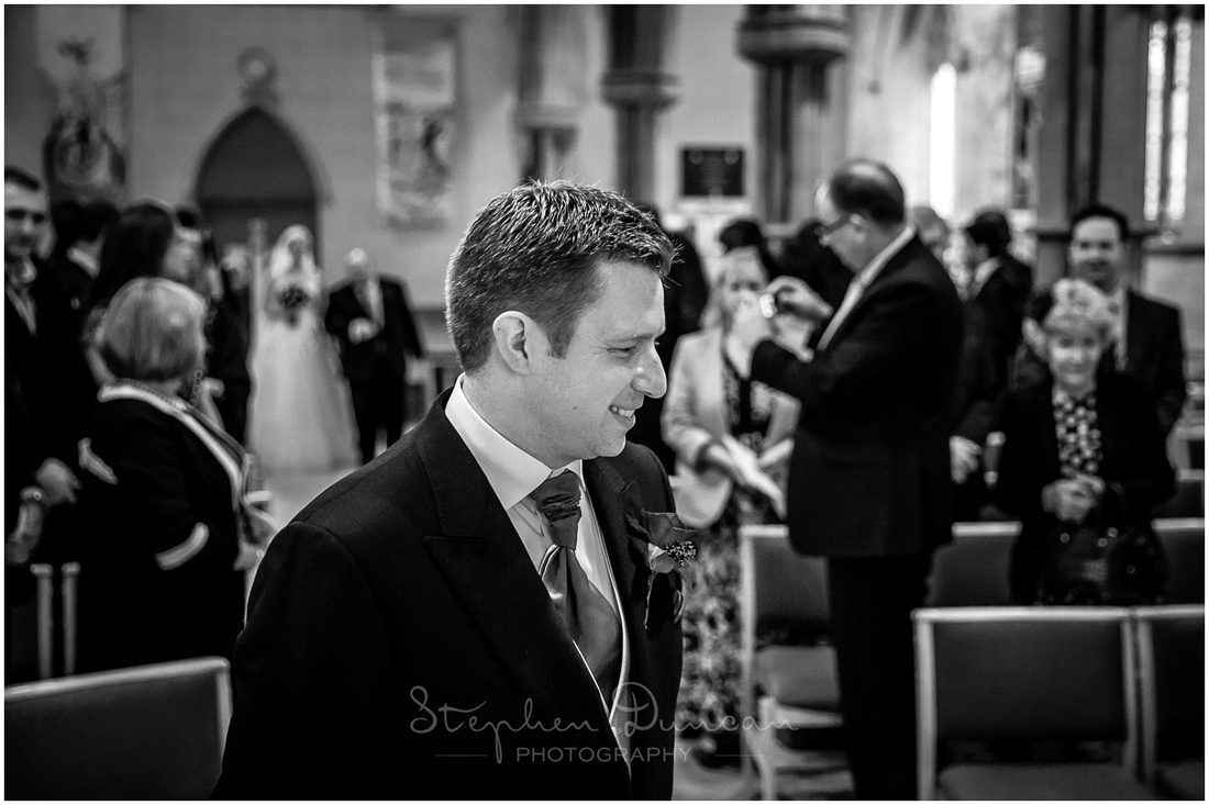 The groom stands at the front of the church as the bride makes her entrance on her father's arm