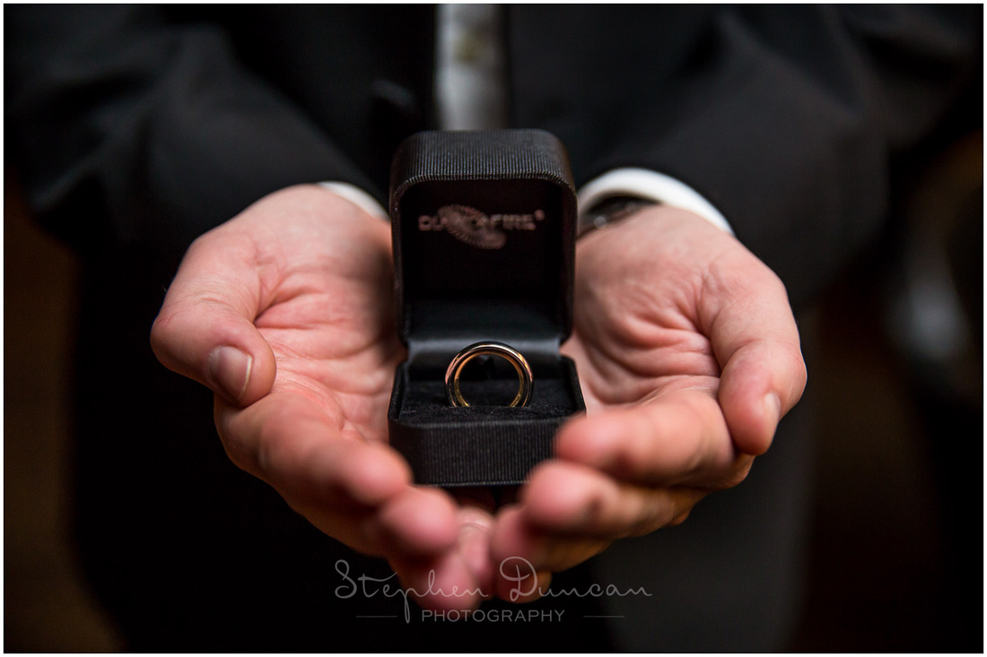 Close-up of wedding rings held by best man