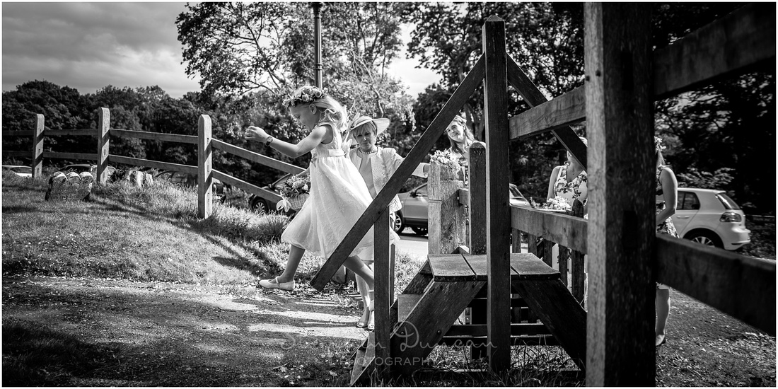 A flower girl excitedly jumps off the gate as the wedding car arrives