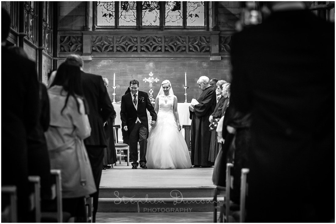 Black and white photo of bride and groom walking down aisle