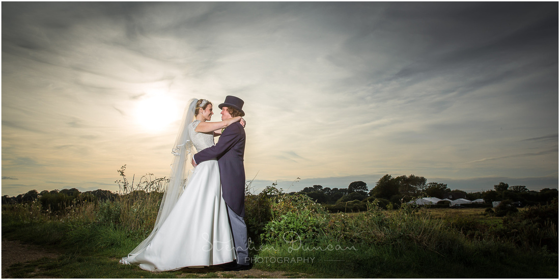 Early evening skies as the newly married couple embrace by the waterside in Lymington