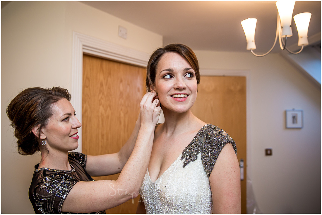 The bridesmaid helps the bride with her jewellery
