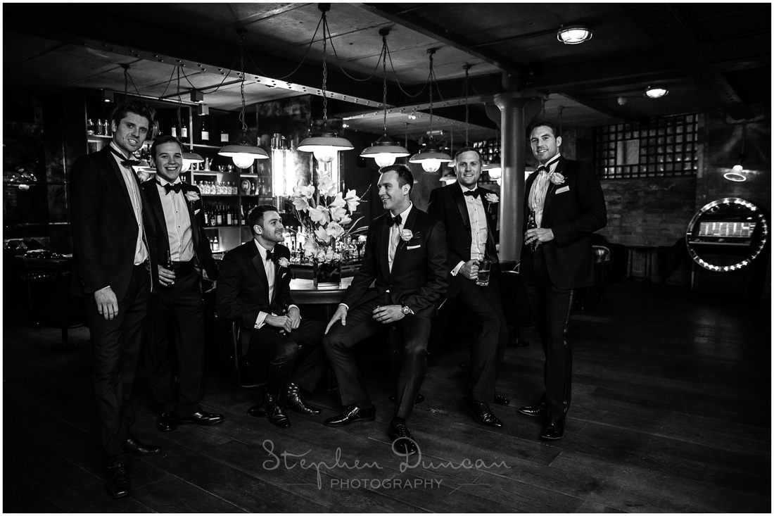 Black and white image of groom with best man and ushers in downstairs cocktail bar at Hixter Bankside