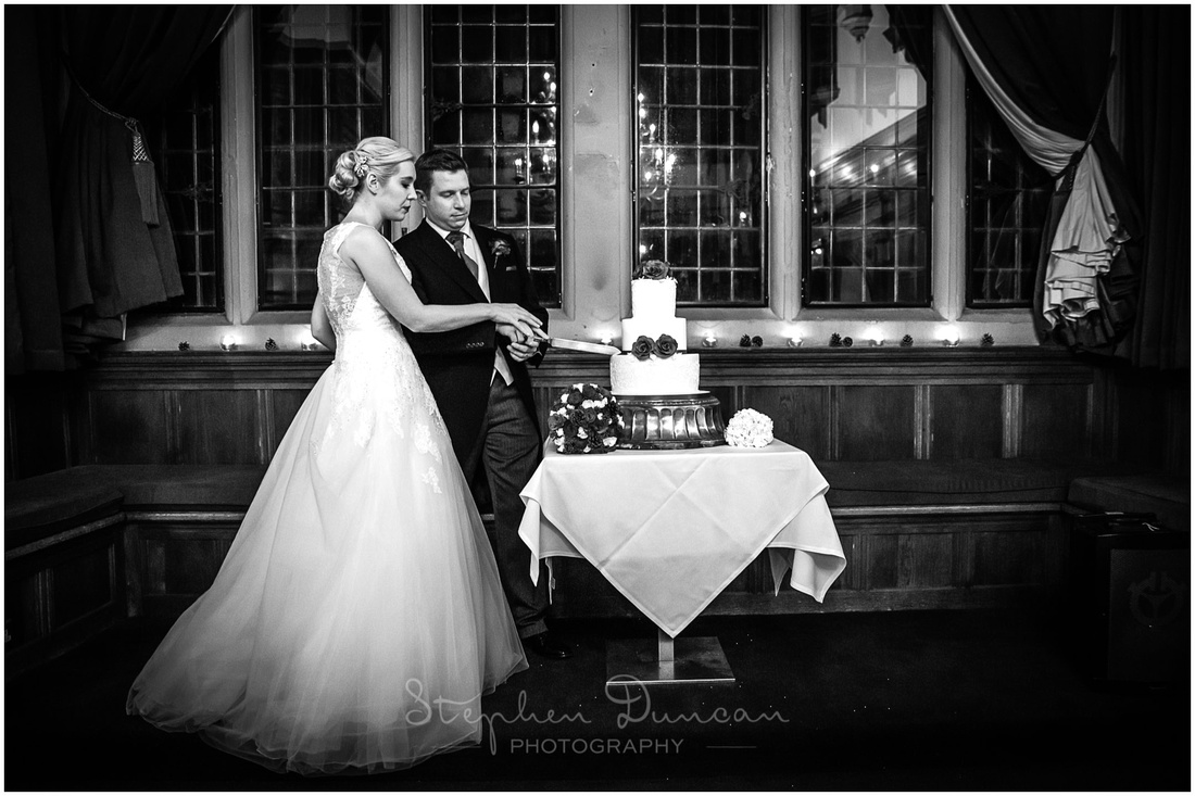 Bride and groom cut cake in dining room