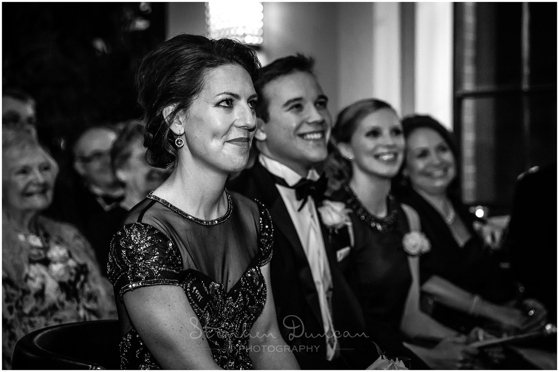Black and white image of bridesmaid looking on at start of wedding ceremony