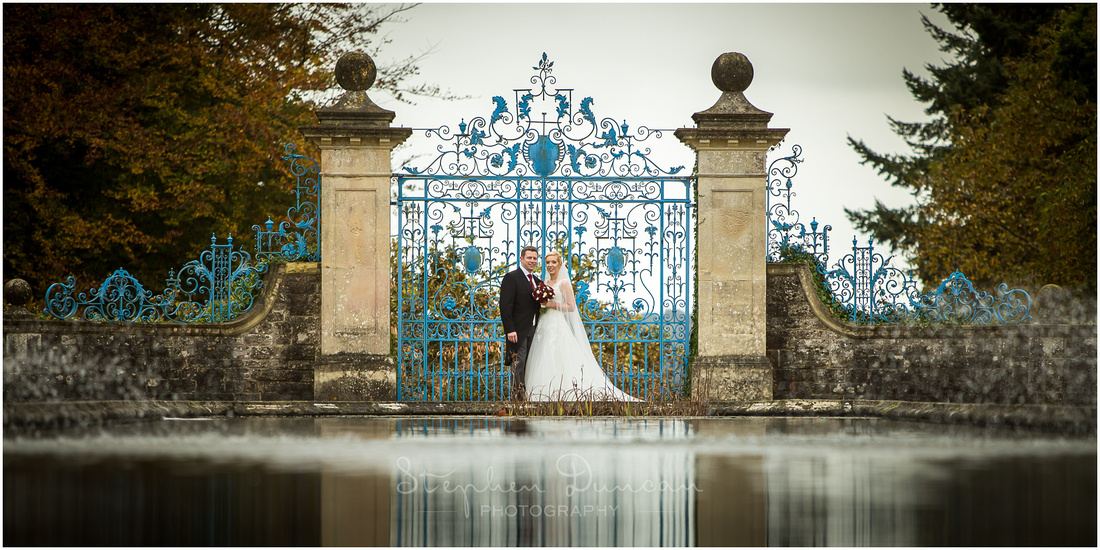 Closer image of couple by blue gates at end of lake in hotel gardens
