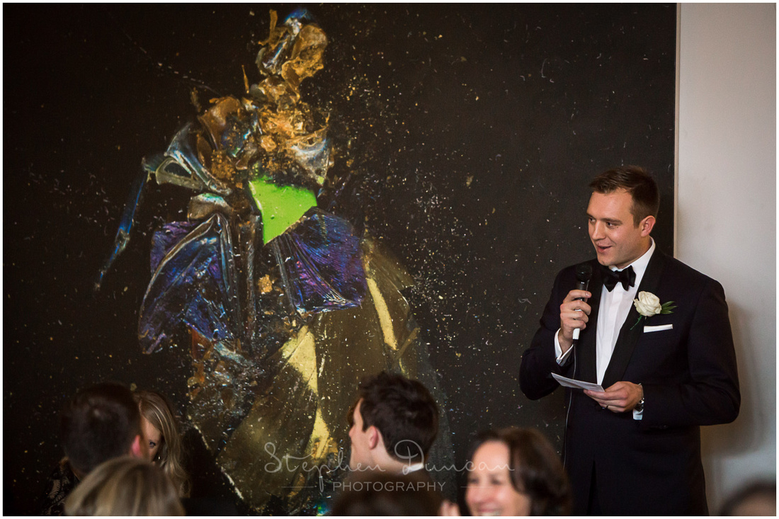 The groom stands in front of one of the restaurant's many pieces of art as he makes his speech