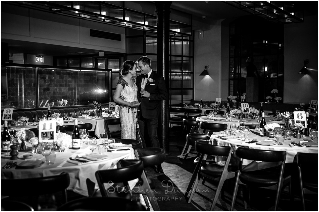 Black and white image of bride and groom in restaurant at Hixter in London
