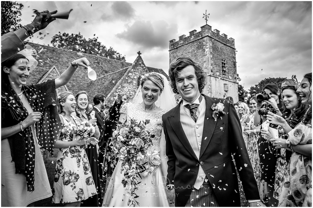 The bride and groom are greeted outside the church with confetti