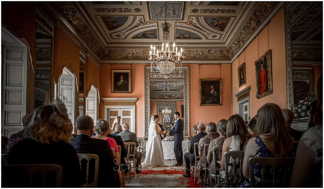 Bride and groom making vows in the opulent ballroom upstairs at Avington Park wedding venue