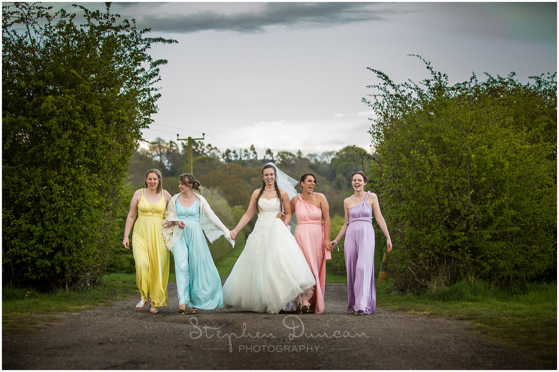 Bride and bridesmaids walk up the lane to the Great Barn reception venue in Titchfield