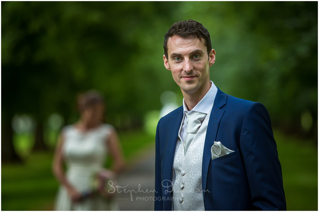 Photograph of groom stood on avenue of trees to the rear of the venue, with bride in the background