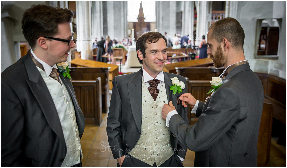 The groom is attended at the front of the church by his two best men