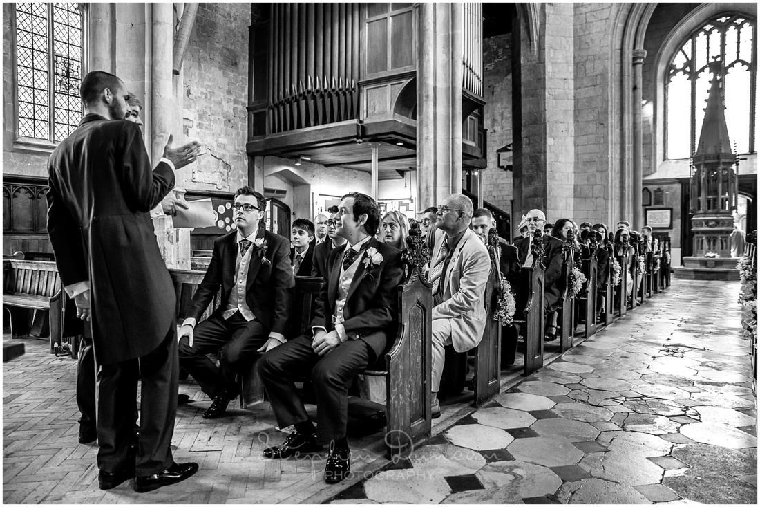 The groom waits with his groomsmen at the front of the church