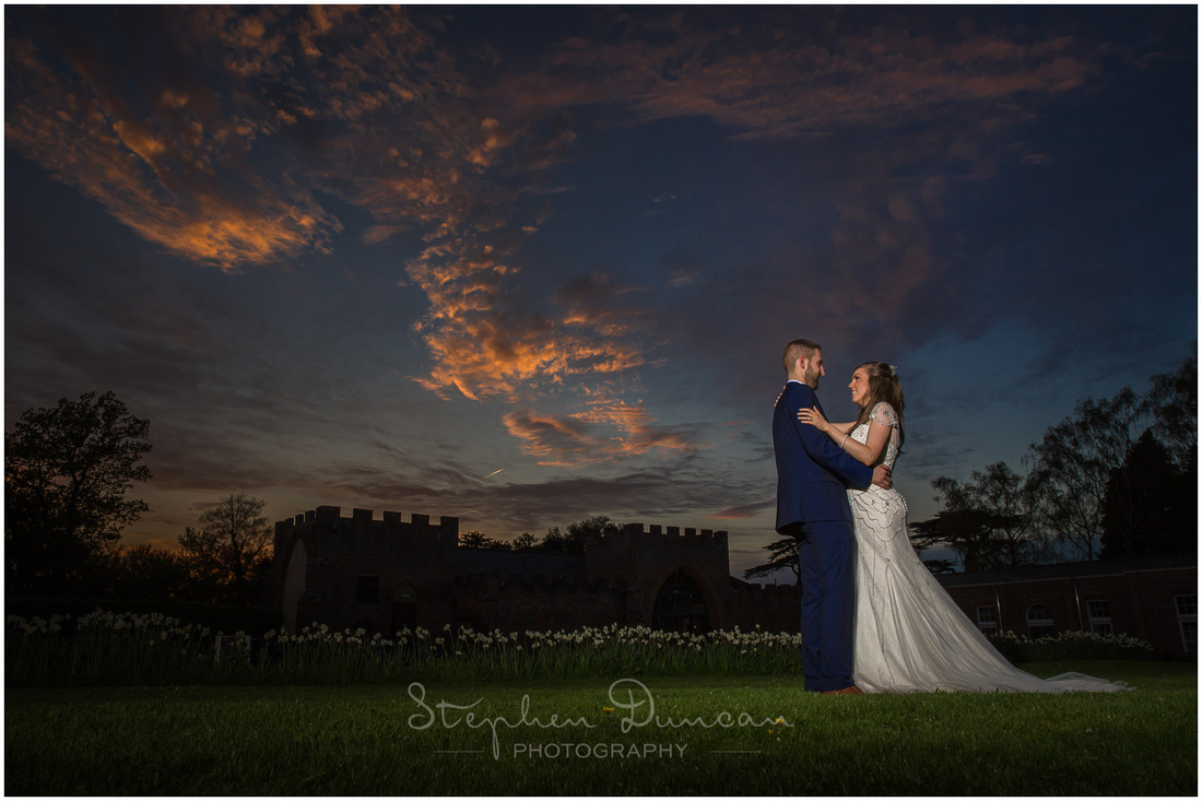 Bride and groom sunset photograph with turret detailing of reception venue in the background