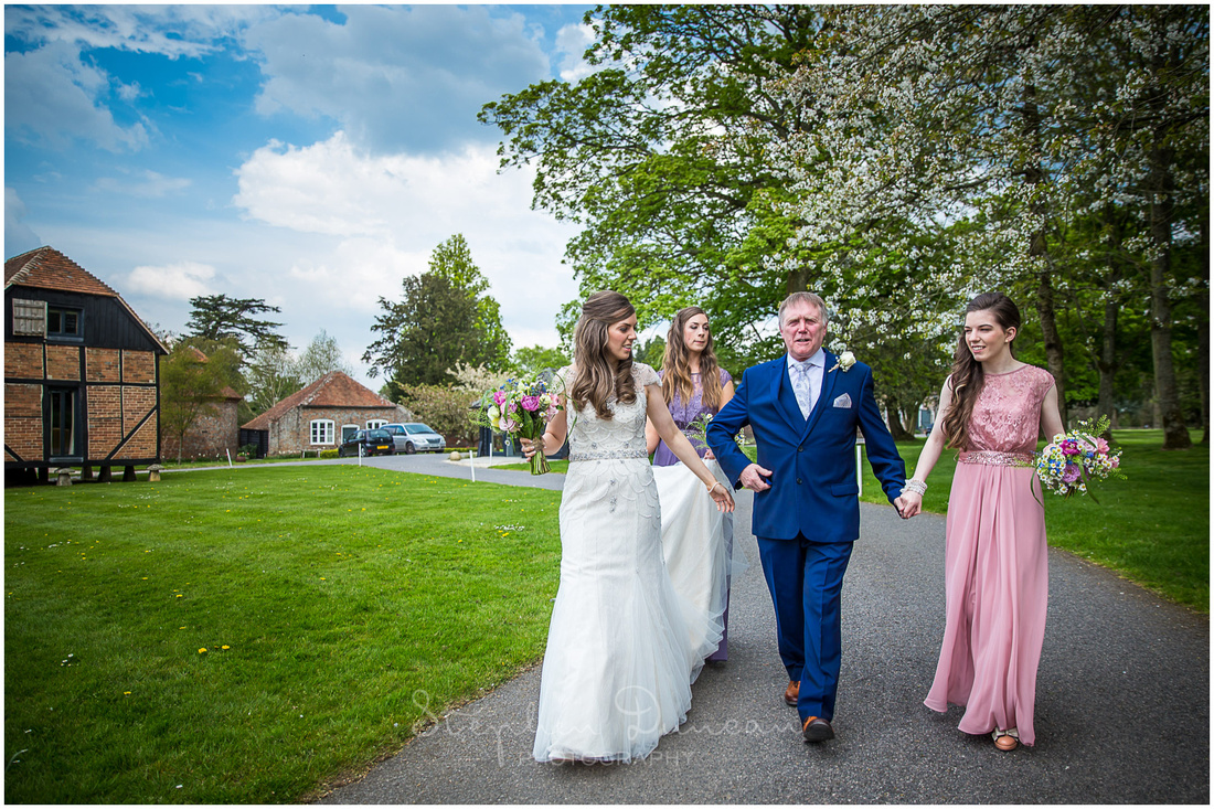 The bride and her father make their way to the ceremony room at Wasing Park on foot from the bridal suite, accompanied by bridesmaids