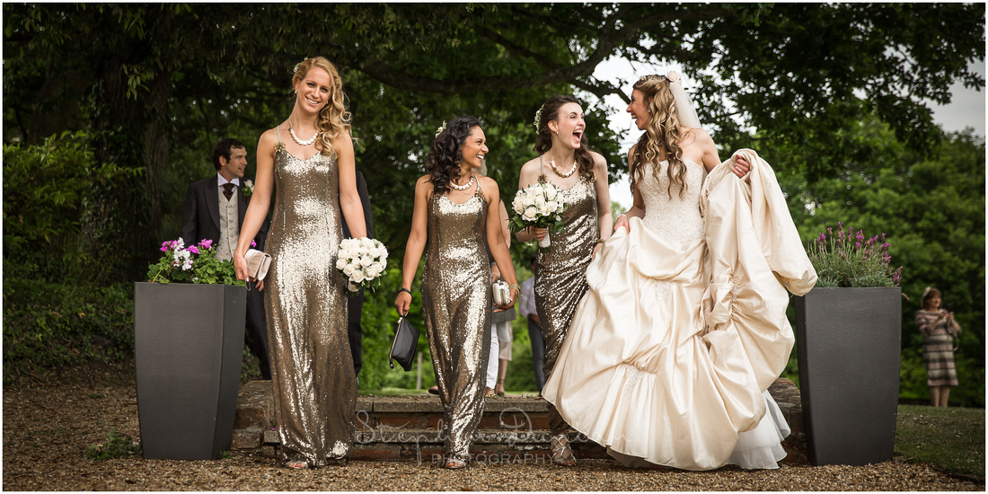 The bride and bridesmaids walk along a gravel path talking together
