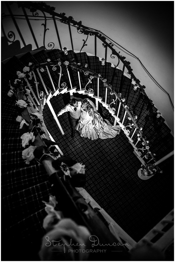 Bride and groom stand by the ornate staircase in the middle of the hotel