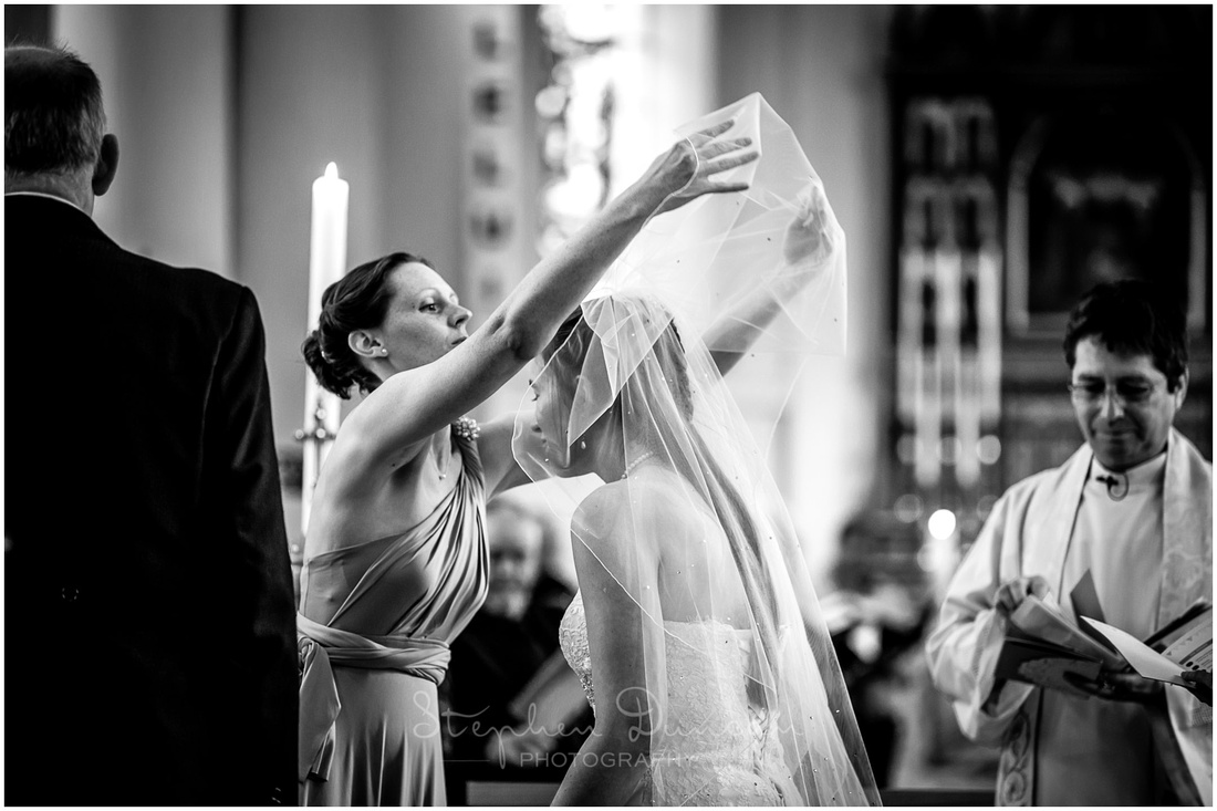 A bridesmaid raises the veil from the bride's face at the start of the marriage ceremony