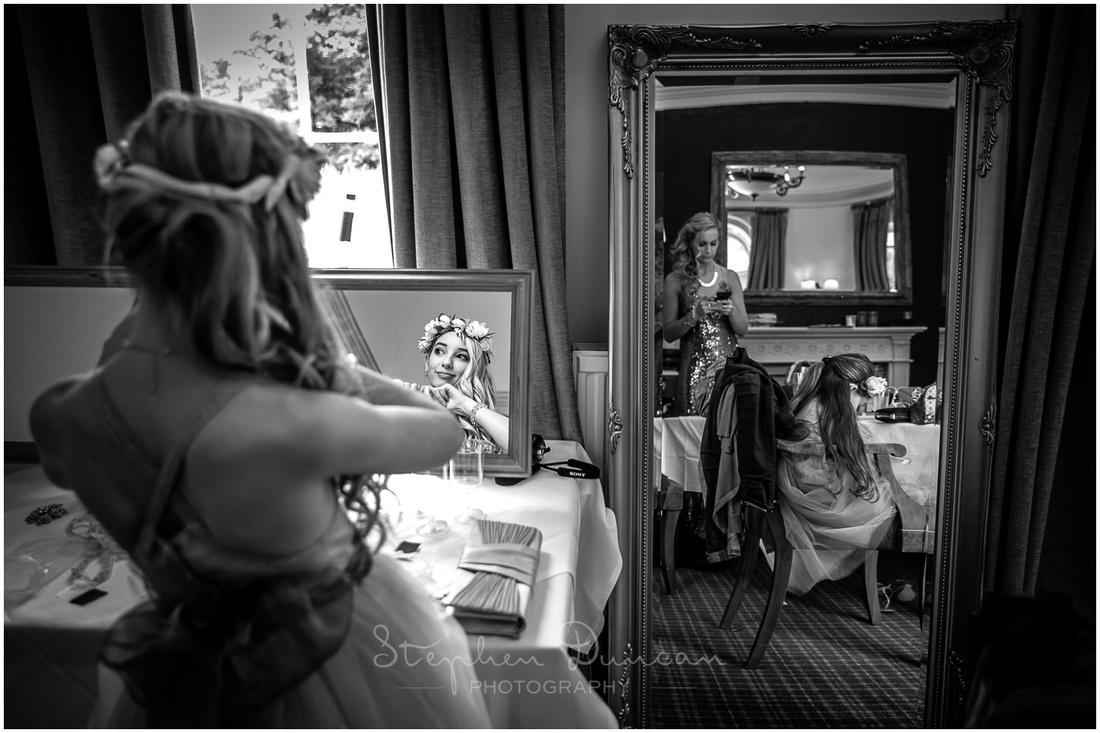 A flower girl looks into a mirror as bride and bridesmaids get ready
